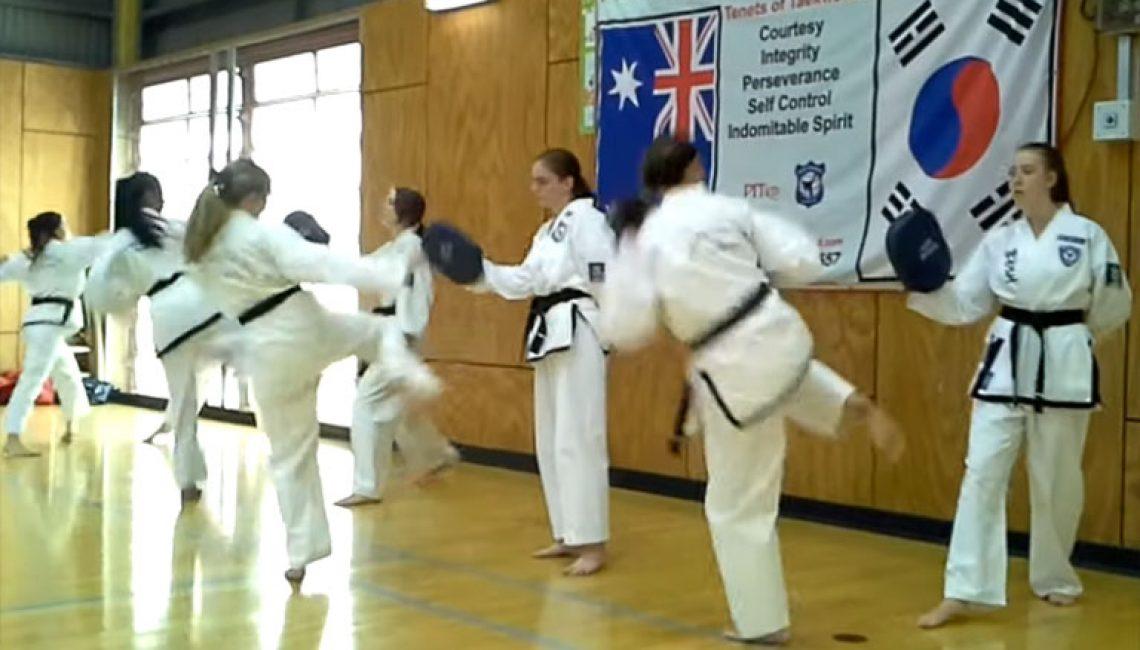 girls practice taekwondo kicks