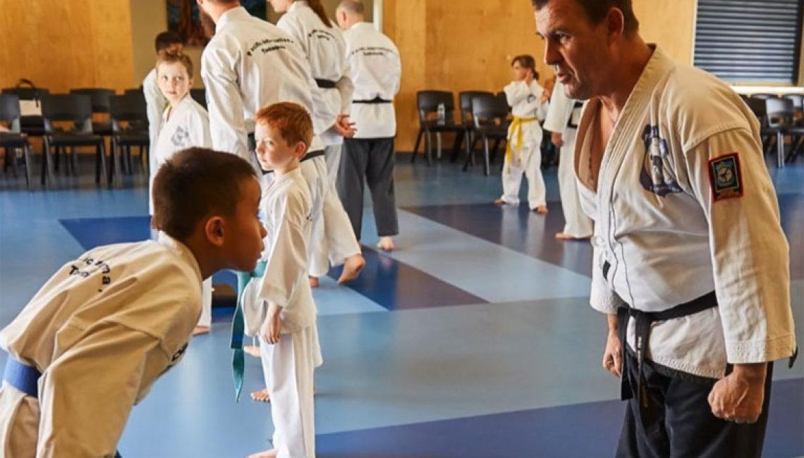 young boy bows to taekwondo instructor
